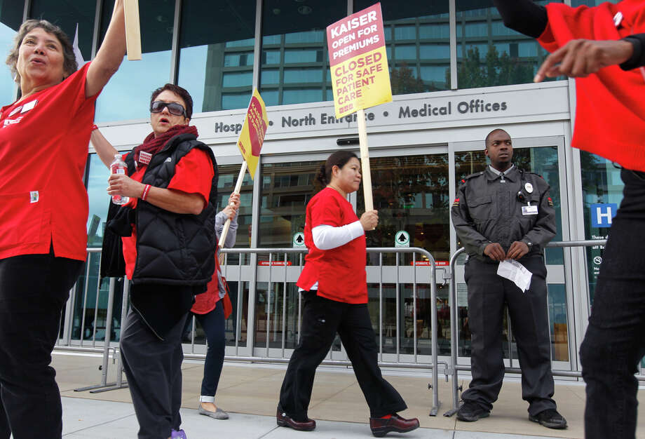 Nurses walk the picket line at Kaiser Permanente Hospital in Oakland as a security guard keeps watch. Photo: Paul Chinn / The Chronicle / ONLINE_YES