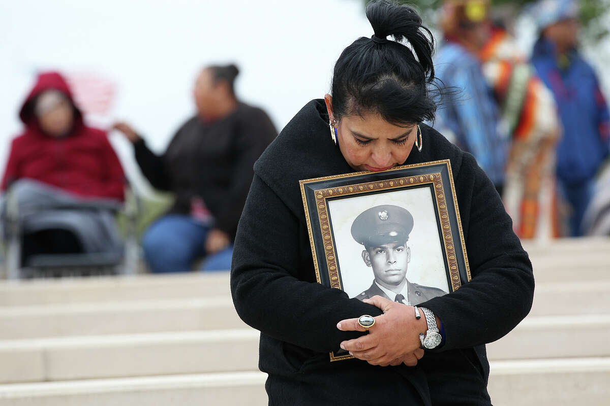Maria Becerra, 53, holds a portrait of her father, U.S. Army veteran Cesario Becerra, before as people gather to honor soldiers and veterans during a Veteran's Day tribute at Fort Sam Houston National Cemetery, Tuesday, Nov. 11, 2014. Becerra's father died five year ago and served two tour during the Vietnam War.
