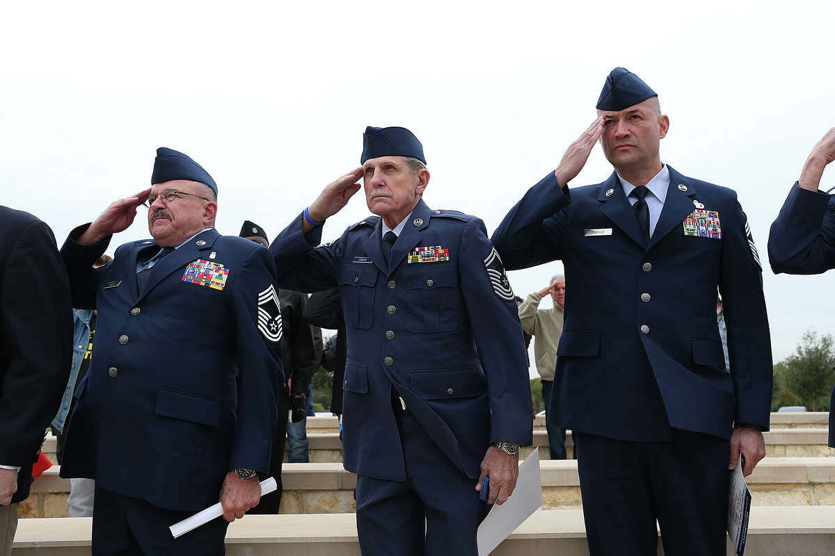 From left, retired Chief Master Sgt. Thomas Hilla, retired Chief Master Sgt. Wendell Cornish and Chief Master Sgt. Pete Padilla salute during a Veteran's Day tribute at Fort Sam Houston National Cemetery, Tuesday, Nov. 11, 2014.