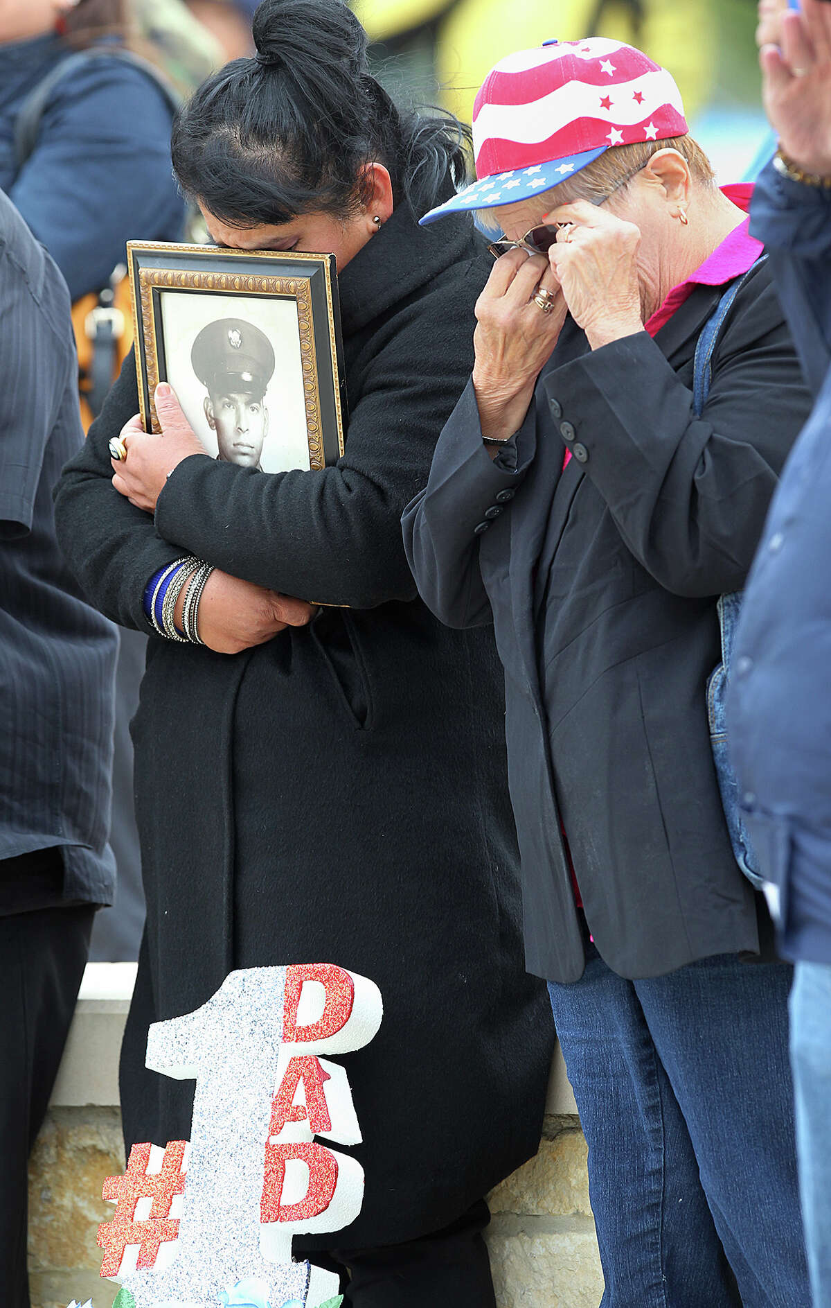 As Taps is played, Maria Becerra, left, and Adelina Shires react during a Veteran's Day tribute at Fort Sam Houston National Cemetery, Tuesday, Nov. 11, 2014. Becerra was holding a portrait of her father, Cesario Becerra, a Vietnam veteran.