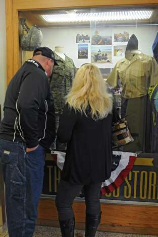 John Cruise of East Greenbush and his wife, Kimberly, look at their sons' uniforms in a display honoring veterans at The College of Saint Rose on Tuesday, Nov. 11, 2014 in Albany, N.Y. They have two sons who are veterans and attend the college. (Lori Van Buren / Times Union) Photo: Lori Van Buren / 00028667A