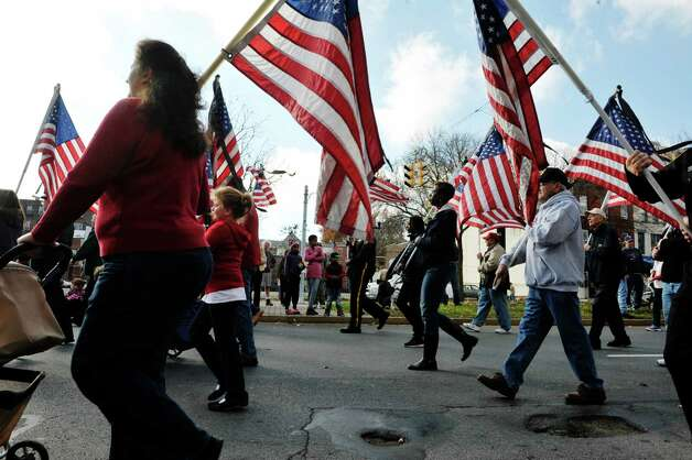 Volunteers with the organization Please Remember Me carry flags as they march in the Albany Veterans Day parade on Tuesday, Nov. 11, 2014, in Albany, N.Y.  Each flag represents 10 Capital Region soldiers killed in action.   (Paul Buckowski / Times Union) Photo: Paul Buckowski / 00029393A