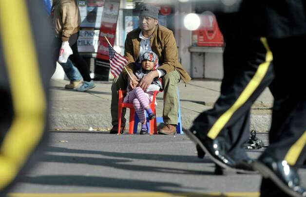 Mohammed Faroque sits with his daughter, Tayba, 5, as they watch the Albany Veterans Day parade from just outside Mohammed's Deshi Bazzar market on Tuesday, Nov. 11, 2014, in Albany, N.Y.   (Paul Buckowski / Times Union) Photo: Paul Buckowski / 00029393A