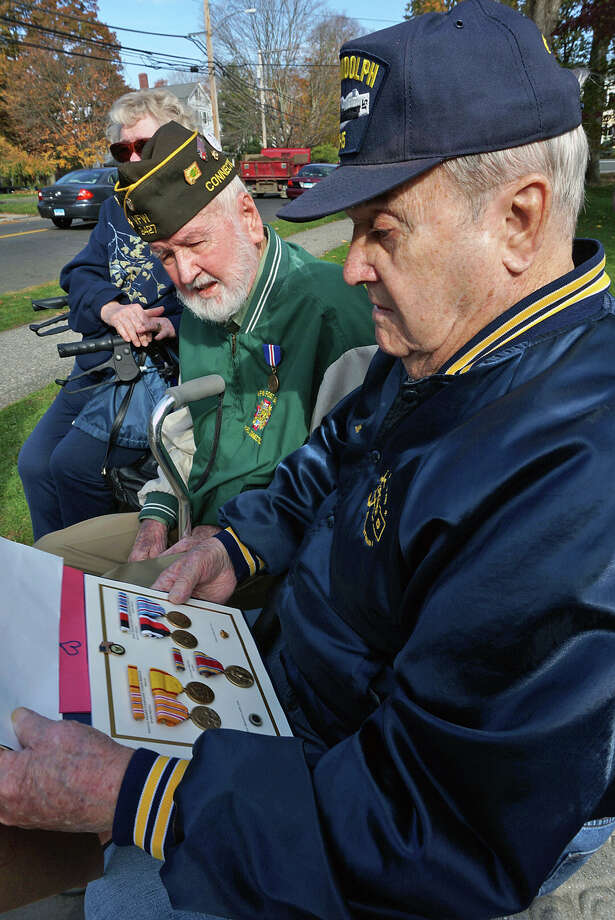 U.S. Navy veteran Milton E. Forstrom, left, shows of the medals he received at Tuesday's Veterans Day ceremonies for his service in World War II to fellow Navy vet Ken Dalling. Photo: Genevieve Reilly / Fairfield Citizen