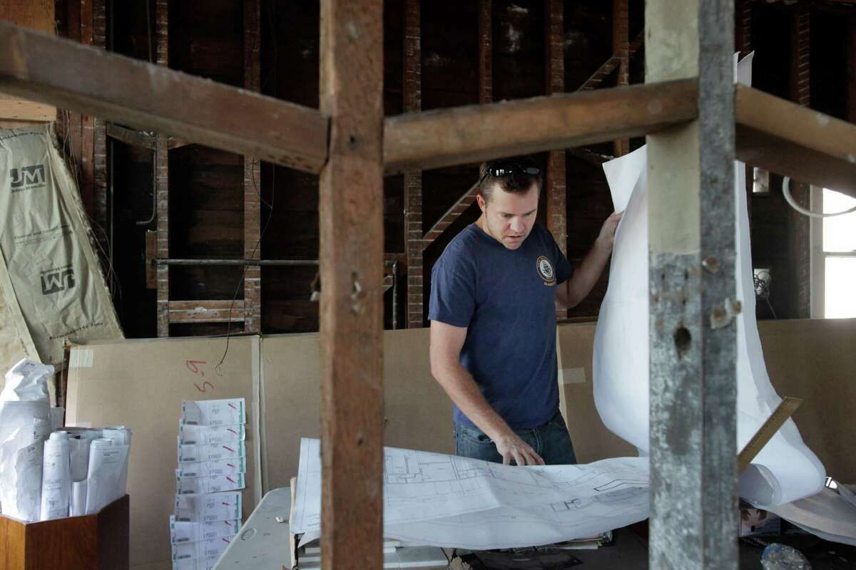 Jeffery inspects the floor plans of a partially finished unit in a recently acquired property on Shotwell Street off 24th.