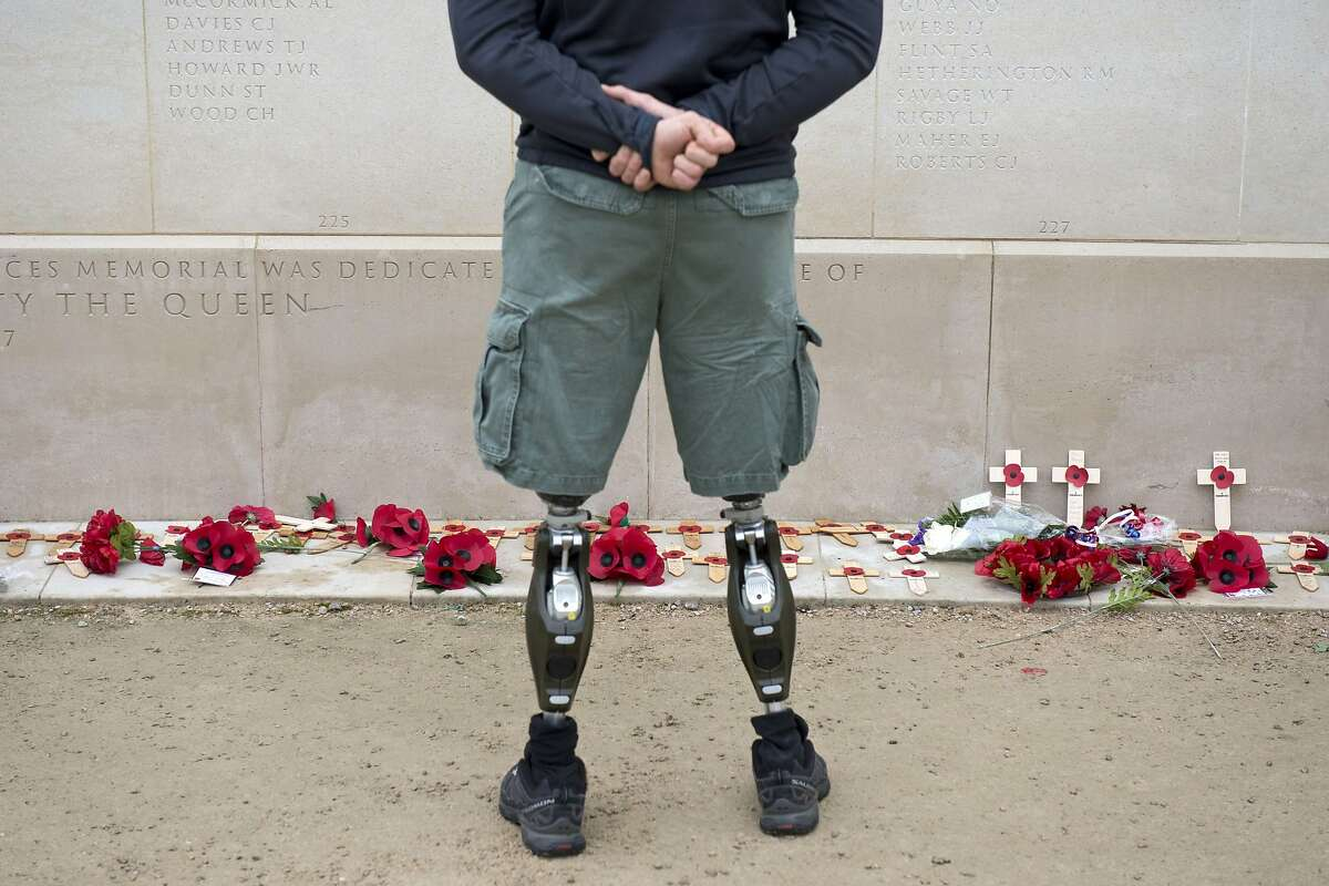 TOPSHOTS A member of the armed forces with prosthetic legs pays his respects at the Armed Forces Memorial in the National Memorial Arboretum on Armistice Day near Lichfield, Staffordshire, central England, on November 11, 2014. In services around the country tributes were paid to the millions of British servicemen and women who have died in conflict since the start of the First World War 100 years ago. November 11 marks Armistice Day, the day on which a ceasefire came into effect in 1918 that ended the First World War on the Western Front. AFP PHOTO / OLI SCARFFOLI SCARFF/AFP/Getty Images