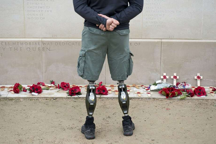 TOPSHOTS A member of the armed forces with prosthetic legs pays his respects at the Armed Forces Memorial in the National Memorial Arboretum on Armistice Day near Lichfield, Staffordshire, central England, on November 11, 2014. In services around the country tributes were paid to the millions of British servicemen and women who have died in conflict since the start of the First World War 100 years ago. November 11 marks Armistice Day, the day on which a ceasefire came into effect in 1918 that ended the First World War on the Western Front.  AFP PHOTO / OLI SCARFFOLI SCARFF/AFP/Getty Images Photo: Oli Scarff, AFP/Getty Images