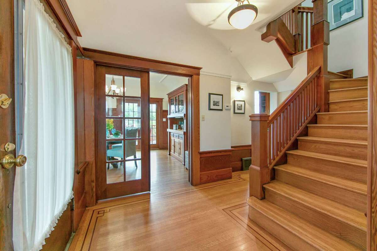 The foyer showcases inlaid hardwood floors and connects to the staircase, dining room and living room.