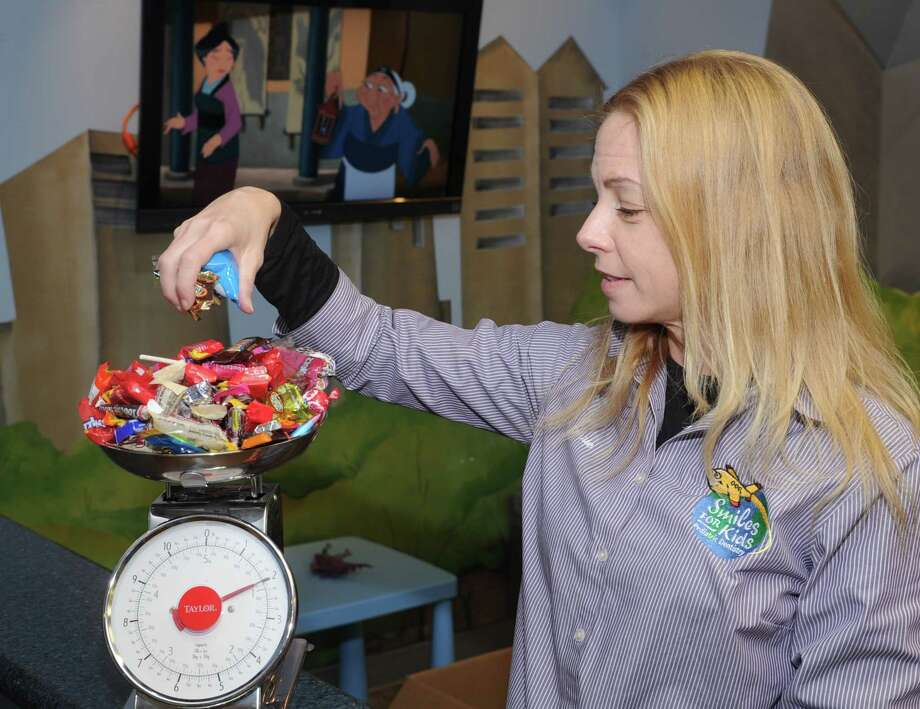 Smiles for Kids Pediatric Dentistry office assistant Carrie Schubert weighs candy to be donated to the troops.Smiles for Kids Pediatric Dentistry office assistant Carrie Schubert weighs candy to be donated to the troops. Photo: Eddy Matchette, Freelance / Freelance