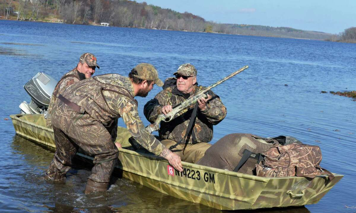 FILE - Setting out for a day of duck hunting on Fish Creek are, from left, Eric Rice, Jared Davis and Bob Hosgood, all of Clifton Park, Tuesday Nov. 11, 2014, in Saratoga Springs, NY. (John Carl D'Annibale / Times Union)