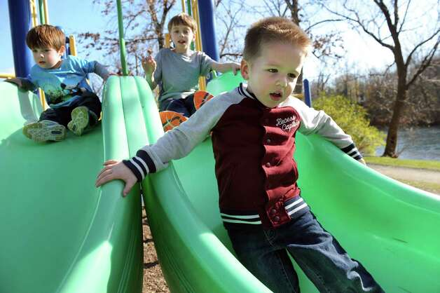 Nico Anthony, 3, of Albany, right, slides while on a play date with Evan Dimaina, 3, of Schenectady, left, and Evan Olori, 9, of Scotia on Tuesday, Nov. 11, 2014, at Buckingham Pond in Albany, N.Y. (Cindy Schultz / Times Union) Photo: Cindy Schultz / 00029431A