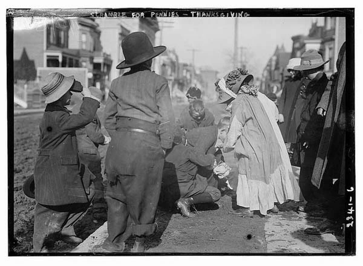 Between 1910 and 1915 : Scramble for pennies on Thanksgiving. This old holiday tradition of