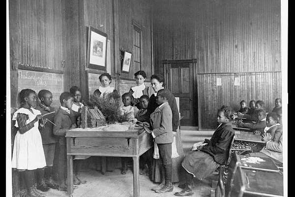 1899 or 1900: Children learning about Thanksgiving, with model log cabin on table, Whittier Primary School, Hampton, Virginia. (Frances Benjamin Johnston)