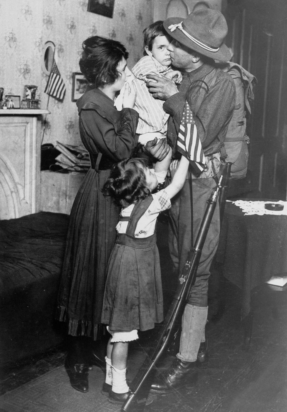 NY National Guardsman Private T. P. Loughlin of 69th New York National Guard Regiment, kissing his little child goodbye as he bids farewell to family before reporting to training camp during WWI, 1917.