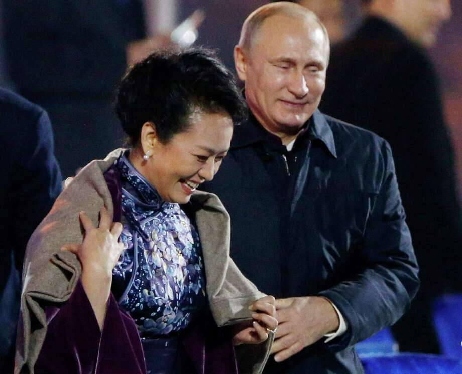 In this Nov. 10, 2014 file photo, Russia's President Vladimir Putin, right, puts a shawl on Peng Liyuan, left, wife of Chinese President Xi Jinping as they arrive to watch a fireworks show after a welcome banquet for the Asia Pacific Economic Cooperation (APEC) summit in Beijing. It was a warm gesture on a chilly night when Vladimir Putin wrapped a shawl around the wife of Xi Jinping while the Chinese president chatted with Barack Obama. The only problem: Putin came off looking gallant, the Chinese summit host gauche and inattentive. (AP Photo, File) CHINA OUT Photo: Associated Press / CHINATOPIX