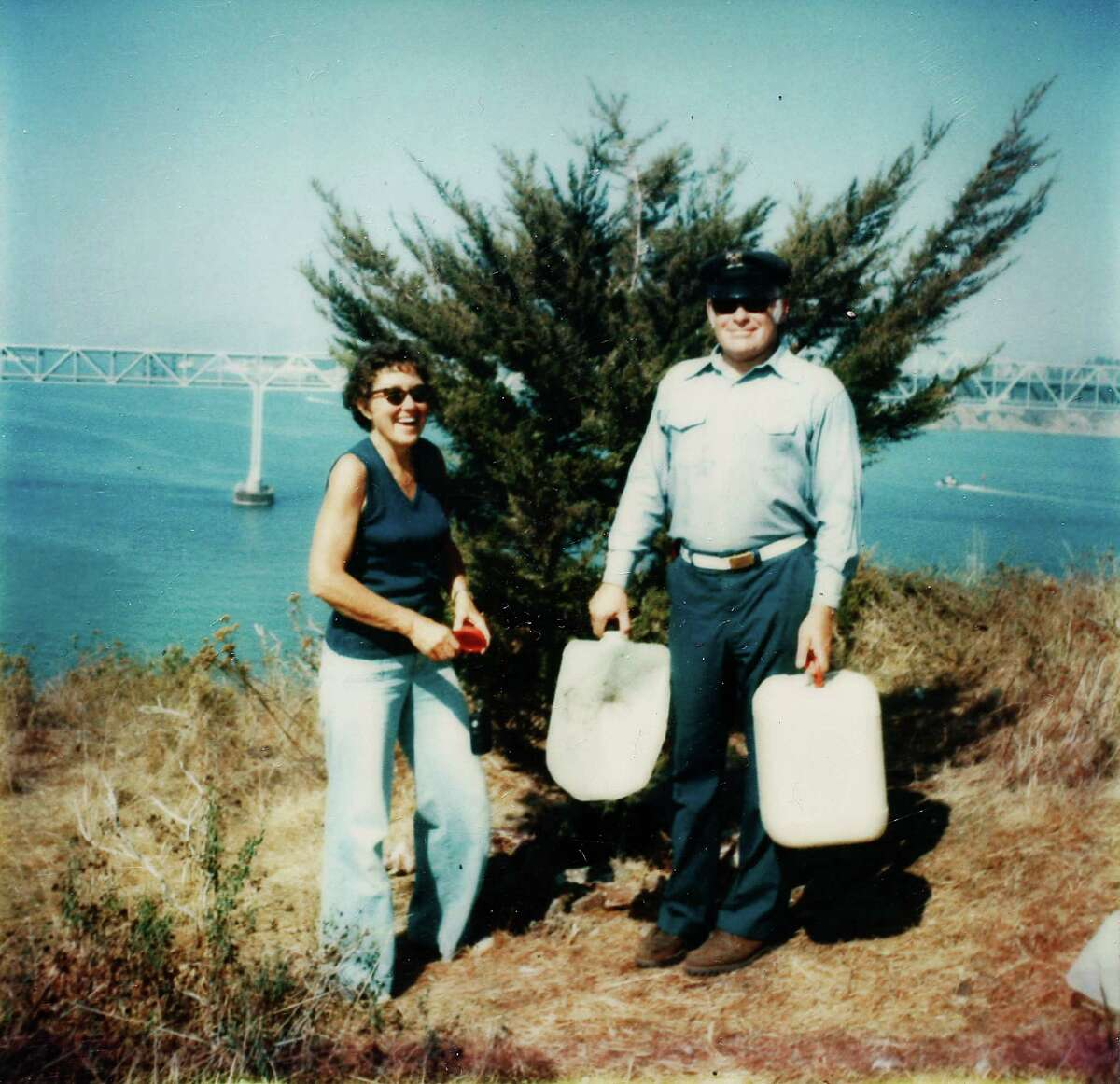A photograph taken in 1979 shows Malcolm Sowers and his wife Helen on top of Red Rock Island in San Pablo Bay after watering a Monterey cypress tree he planted on the barren island.