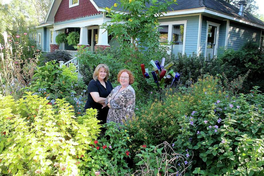 Dee Melancon and Brenda Eskelson take pride in efforts to beautify the Heights, exemplified by the gardens at Eskelson's home on 12th Street, which was featured on a garden tour in October. Photo: Pin Lim, Freelannce / Copyright Pin Lim.