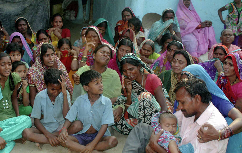 Relatives mourn the death of women who died after undergoing sterilization surgeries, at a village near Bilaspur, in the central Indian state of Chhattisgarh. Photo: Associated Press / Press Trust of India