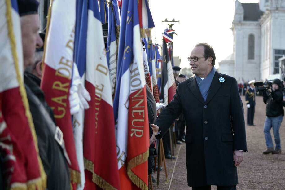 French President Francois Hollande (R) shakes hand with veterans during a ceremony at the Notre-Dame-de-Lorette war memorial on November 11, 2014 in Ablain-Saint-Nazaire, northern France, as part of the Armistice Day ceremonies marking the 96th anniversary of the end of World War I.  AFP PHOTO / LIONEL BONAVENTURELIONEL BONAVENTURE/AFP/Getty Images Photo: LIONEL BONAVENTURE / AFP/Getty Images / AFP
