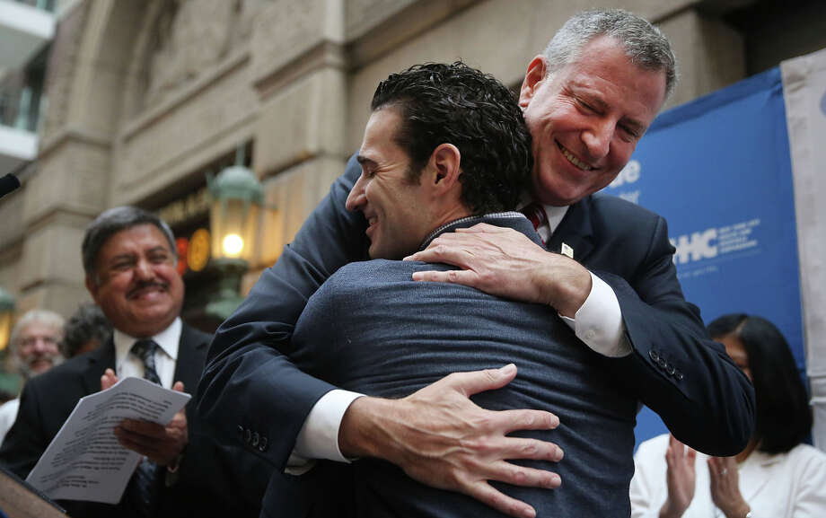 Dr. Craig Spencer (foreground) receives a hug from New York Mayor Bill de Blasio, who praised the physician for his work with Ebola patients in Africa. Photo: Spencer Platt / Getty Images / 2014 Getty Images