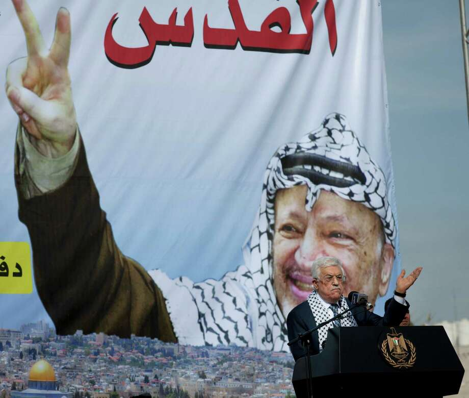 "Palestinian President Mahmoud Abbas addresses supporters during a ceremony marking the 10th anniversary of the late Palestinian leader Yasser Arafat's death, at the his headquarters in the West Bank city of Ramallah, Tuesday, Nov. 11, 2014. Abbas on Tuesday accused Israel of provoking a ""religious war"" as new violence between the sides broke out in the West Bank, leaving a Palestinian man dead, amid mounting concerns that their long-running conflict is entering a new and dangerous phase. A poster with a picture of Arafat contains Arabic that reads, ""Jerusalem."" (AP Photo/Nasser Nasser) Photo: Nasser Nasser / Associated Press / AP"