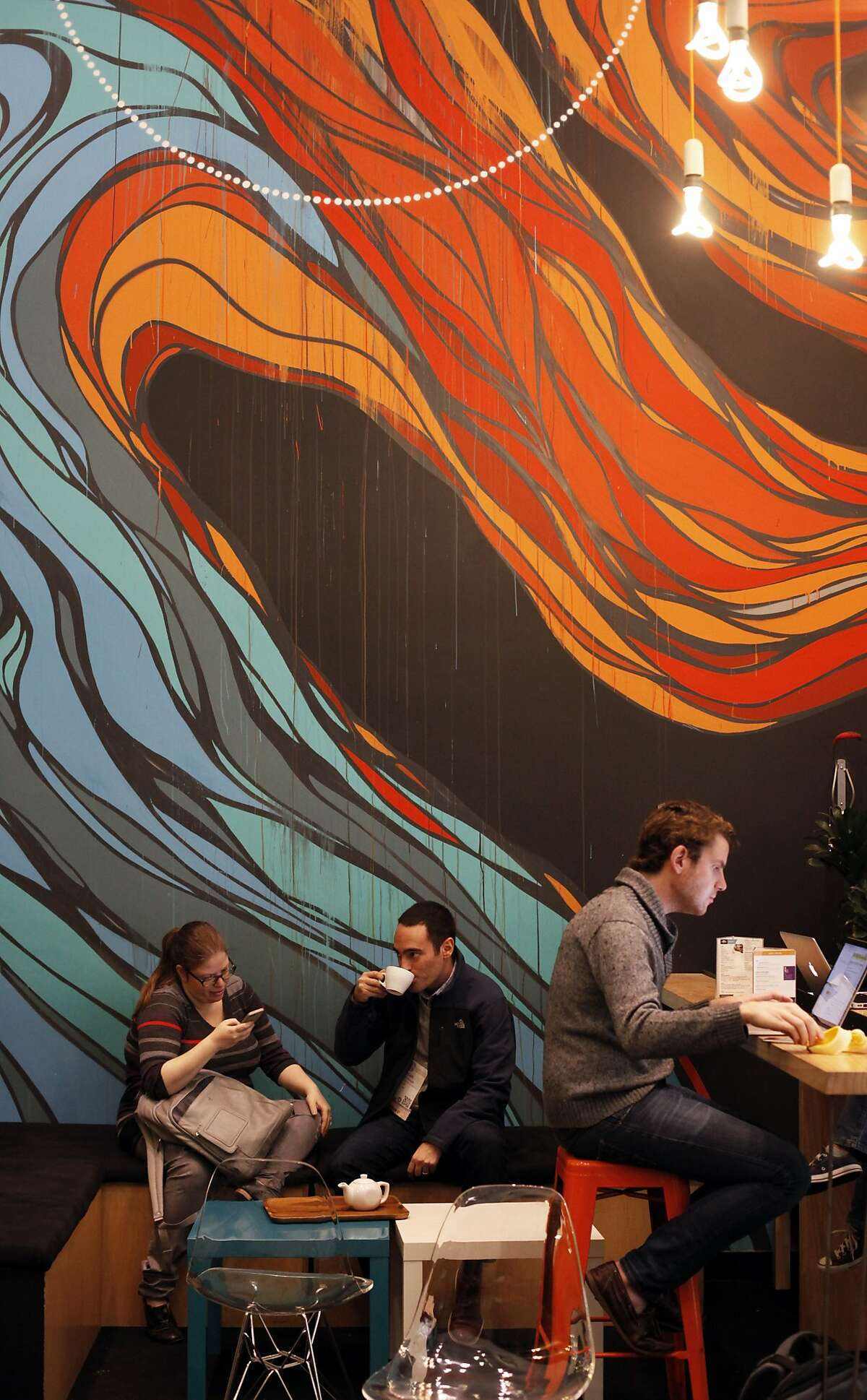Patrons work and drink tea at Workshop Cafe on November 11, 2014 in San Francisco, Calif. Behind them is a mural by local artist Erick Otto.
