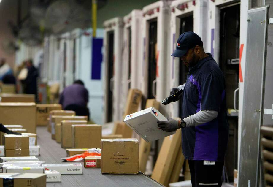 A FedEx courier scans a package at the company's warehouse on Holly Hall Drive last year, when FedEx reported Cyber Monday was extremely busy. (Cody Duty / Houston Chronicle) Photo: Cody Duty, Staff / © 2013 Houston Chronicle