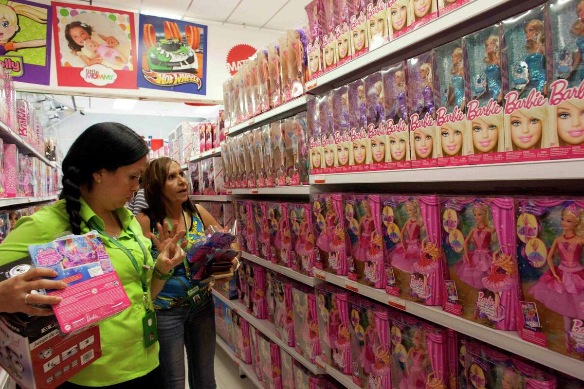 Shoppers look over the selection of Barbies in a Caracas store. Venezuela has decreed that the dolls must sell at deep discounts for the holidays.