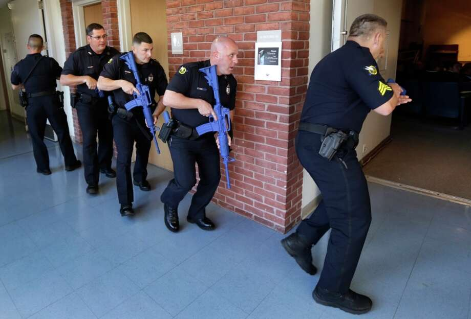 Methuen police carry training weapons as they search the halls of a school during a demonstration. Photo: Charles Krupa / Associated Press / AP