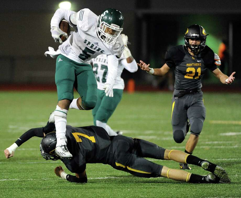 Spring running back Xavier Jones (5) leaps over Klein Oak defensive back Jacob Harper (7) as defensive Jacob Weaver (21) looks on during the second half of a high school football game, Thursday, November 6, 2014, at Klein Memorial Stadium in Houston. (Photo: Eric Christian Smith/For the Chronicle) Photo: Eric Christian Smith, Freelance / 2014 Eric Christian Smith