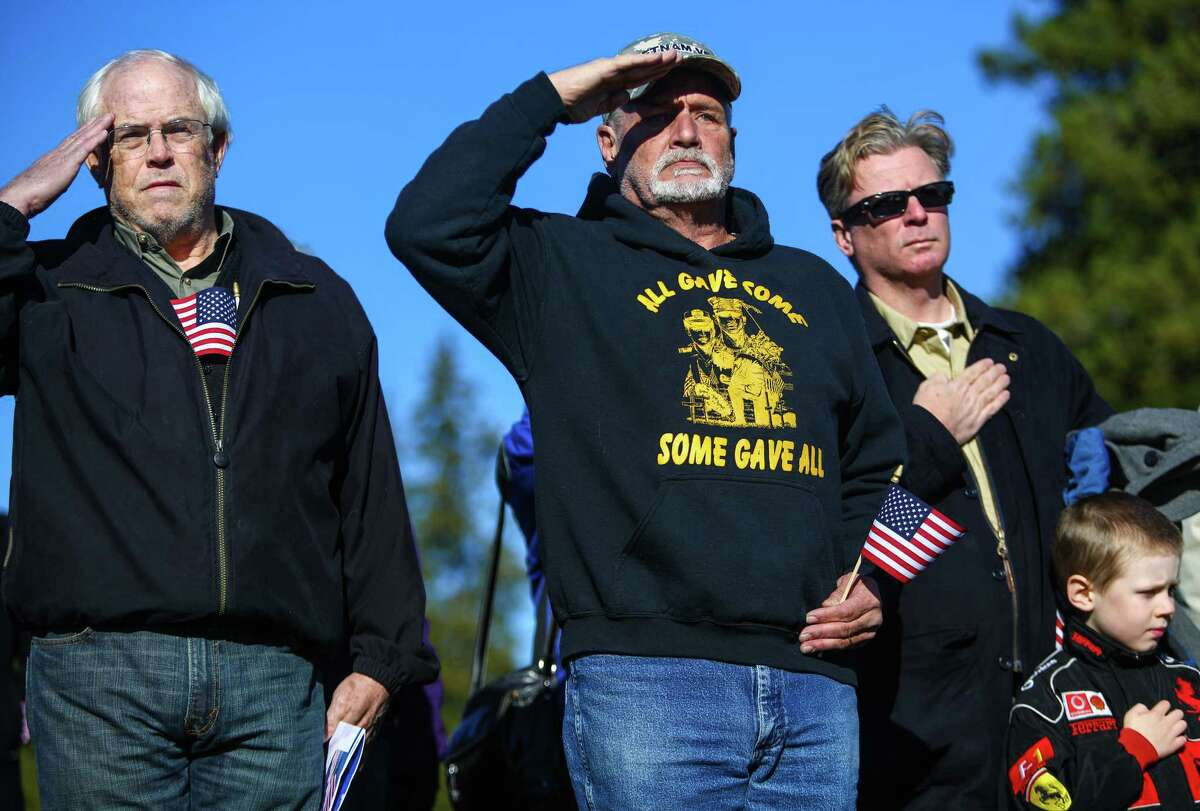 Vietnam veteran Donald Ackerman, center, salutes during a ceremony at Evergreen Washelli Cemetery honoring past and current military members on Veterans Day.
