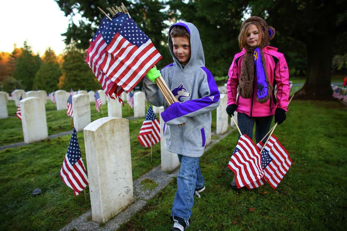 Allen Eddleman, 8, and Aurora Gregorich, 9, place flags during sunrise at Evergreen Washelli Cemetery. Thousands of flags were placed there by Boy Scouts and Girl Scouts in advance of a Veterans Day ceremony. Photographed on Tuesday, November 11, 2014.