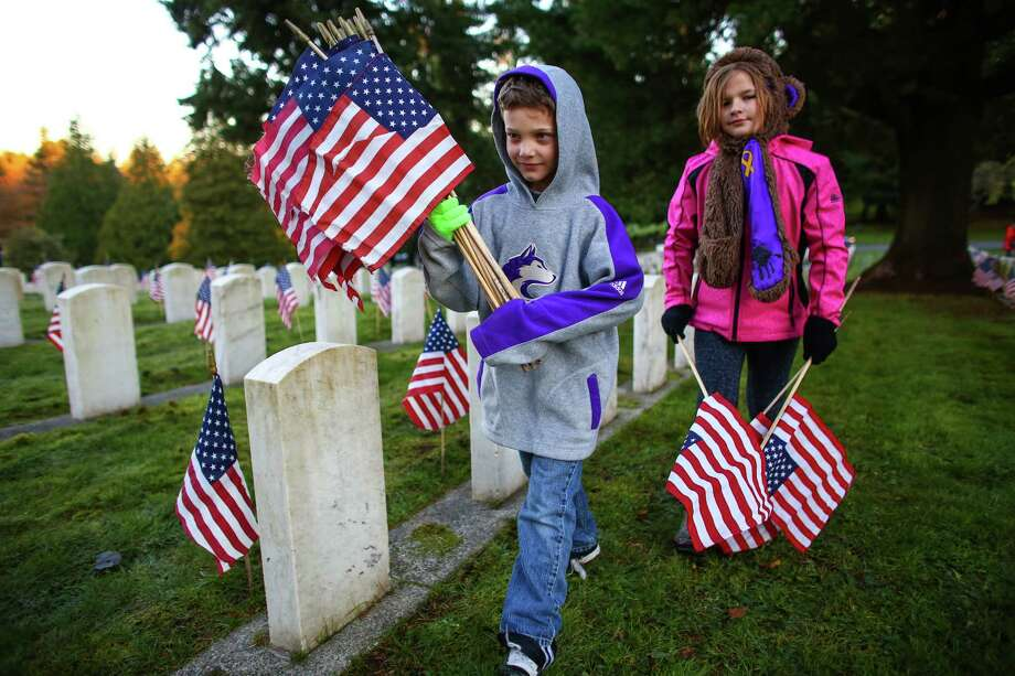 Allen Eddleman, 8, and Aurora Gregorich, 9, place flags during sunrise at Evergreen Washelli Cemetery. Thousands of flags were placed there by Boy Scouts and Girl Scouts in  advance of a Veterans Day ceremony. Photographed on Tuesday, November  11, 2014. Photo: JOSHUA TRUJILLO, SEATTLEPI.COM / SEATTLEPI.COM