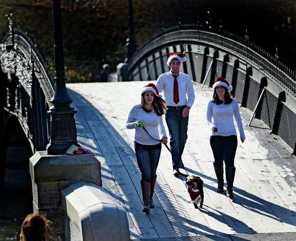 Erin Niblo, left Jared Stephens, center and Nikki Gallant walk over the Washington Park bridge Tuesday afternoon Nov. 11, 2014 decked out in their Christmas outfits on route to getting their Christmas Card photos made in Albany, N.Y.  With them is their dog Sweet Pea.      (Skip Dickstein/Times Union) Photo: SKIP DICKSTEIN