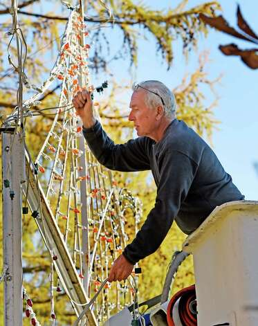 Mike Hartmann of Schenectady Hardware and Electric donates his time as he works on the Capital Holiday Lights display in warmer than normal temperatures Tuesday afternoon Nov. 11, 2014 in Washington Park in Albany, N.Y.  The Holiday Lights display will have it's earliest opening ever with a sneak peek walk-thru on Nov. 20-22 and will be followed by a Chili, Chowder & Soup Fest on Nov. 23 from 4-8 p.m. proceeds going to various charities locally.  The display will have it's grand opening on Nov. 28th at 6 p.m.   (Skip Dickstein/Times Union) Photo: SKIP DICKSTEIN