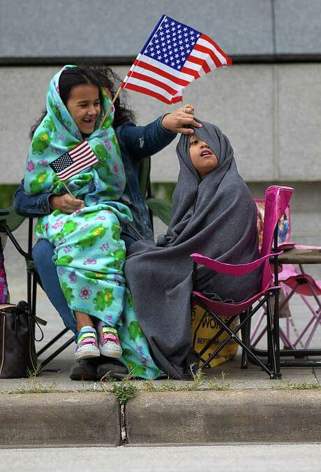 Rebekah Solis, 7, giggles as mom, Angelita, helps sister, Elena, 9, see at the veterans parade. Photo: Johnny Hanson, Staff / © 2014  Houston Chronicle
