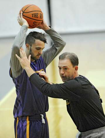 Peter Hooley holds the ball above his head while coach Will Brown demonstrates the next drill during the first basketball practice of the season for the UAlbany men on Thursday, Oct. 9, 2014 in Albany, N.Y. (Lori Van Buren / Times Union) Photo: Lori Van Buren / 10028939A