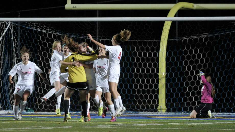 Fairfield Warde celebrates the game winning goal, scored with 21.4 seconds left in the CIAC State Class LL girls soccer semifinals game between Fairfield Warde and Ridgefield high schools, palyed at Newtown High School, Newtown, Conn, on Tuesday, November 11, 2014. Ridgefield goalkeeper Julia Middlebrook (1) is behind them. Photo: H John Voorhees III / The News-Times