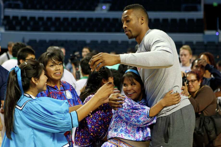 Dwight Howard is a hit south of the border as he is embraced by players from the Tarahumaras basketball team during a clinic with the Rockets and Timberwolves on Tuesday in Mexico City. The Tarahumaras are a Native American people of northwestern Mexico. Photo: Dario Lopez-Mills, STF / AP