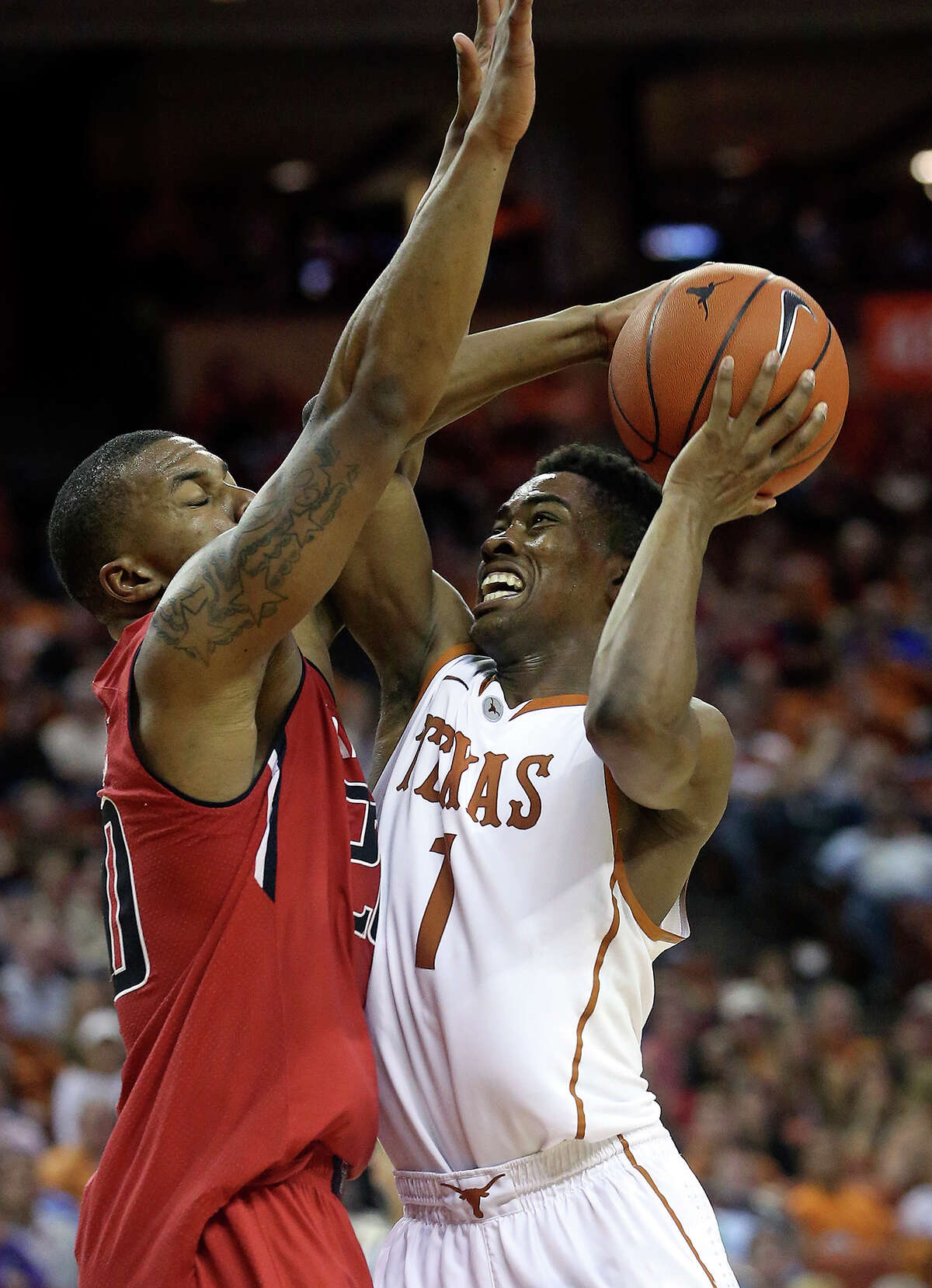 UT guard Isaiah Taylor takes a shot under the basket against Texas Tech's Toddrick Gotcher at the Frank Erwin Center in Austin on January 11, 2014. Taylor is expected to be a key piece to the Longhorns offense in 2014-15.
