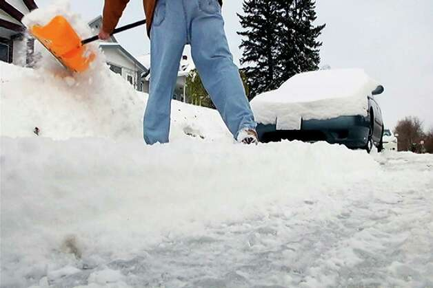 A Duluth, Minn. resident shovels the snow from in front of a vehicle, Tuesday, Nov. 11, 2014,  following the season's first measurable snowfall on Monday. Some areas of Minnesota recorded over one foot of snow. (AP Photo/WDIO-TV, Carl Sauer) ORG XMIT: MNDIO101 Photo: Carl Sauer / WDIO-TV