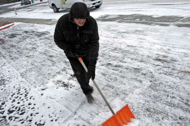 Local resident Tim Castro clears a parking lot in Billings, Mont., Tuesday, Nov. 11, 2014. Forecasters said record low temperatures were possible Wednesday morning after a cold front dropped down from Canada. (AP Photo/Matthew Brown) ORG XMIT: RPMB102 Photo: Matthew Brown / AP