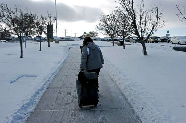Traveler Susan Messerly returns to her car at Billings Logan International Airport in Billings, Mont., after her flight to Phoenix was canceled, as temperatures plunged below zero in Billings, Mont., Tuesday, Nov. 11, 2014. Forecasters said record lows were possible Wednesday morning and the cold air would linger into the weekend. (AP Photo/Matthew Brown) ORG XMIT: RPMB101 Photo: Matthew Brown / AP