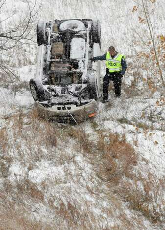 Officer Alex Colburn of the Colorado State Police investigates a rollover off of an embankment of the Hwy. 24 Bypass in Colorado Springs, Colo., on Tuesday, Nov.11, 2014. The passenger was standing next to the car when the officer arrived. This wreck and numerous other wrecks were caused by icy roads in Colorado Springs.  (AP Photo/The Gazette, Jerilee Bennett) ORG XMIT: COCOL106 Photo: Jerilee Bennett / The Gazette