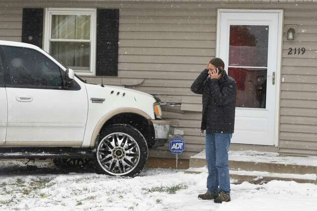 Homeowner Terri Loughlin talks to an agent for her insurance company after an SUV slid into her house in Colorado Springs, Colo., Tuesday, Nov. 11, 2014. Temperatures are forecasted to not get out of the 20's today in Colorado Springs. (AP Photo/The Colorado Springs Gazette, Jerilee Bennett) MAGS OUT  ORG XMIT: COCOL102 Photo: Jerilee Bennett / The Colorado Springs Gazette