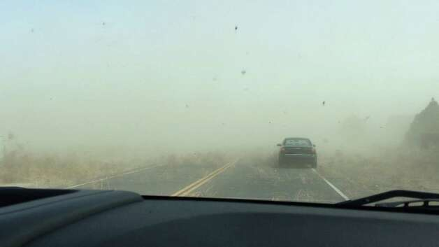 This photograph provided by Brian Paulson shows a dust storm carrying tumbleweeds on the road near Pueblo West, south of Colorado Springs, Colo., Tuesday, Nov. 11, 2014. The arctic air mass affecting the central United States and Rockies kicked up tumbleweeds and dust as it blew across Colorado. (AP Photo/Brian Paulson) ORG XMIT: LA109 Photo: Brian Paulson / Brian Paulson