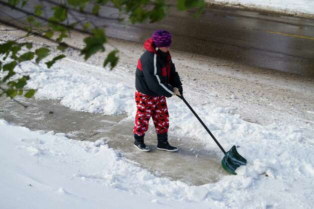 Ana Pena shovels the sidewalk in front of her house Tuesday, Nov. 11, 2014, in Minneapolis, Minn. Pena says the icy surface makes it hard to shovel. Forecasters say round two of the storm will bring frigid temperatures which should stay below freezing for the remainder of the week. (AP Photo/Minnesota Public Radio, Yi-Chin Lee) ORG XMIT: MNMPR201 Photo: Yi-Chin Lee / Minnesota Public Radio