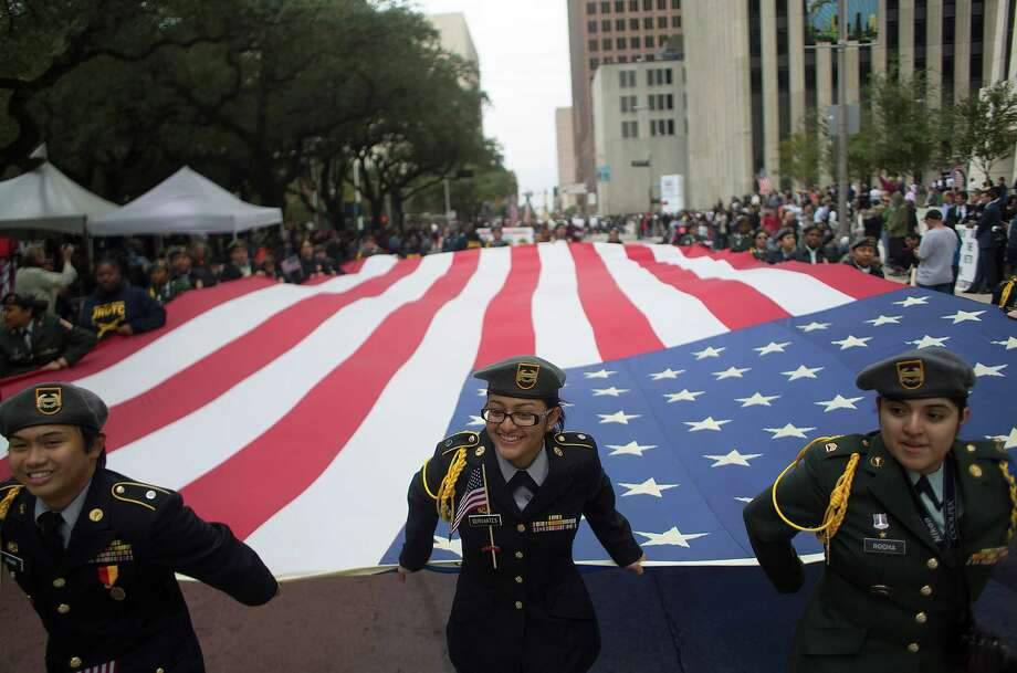 Milby High School JROTC cadets carry a proud load Tuesday as they make their way down Smith Street during the Houston Salutes American Heroes - Veterans Day Parade, which drew thousands downtown. Photo: Johnny Hanson, Staff / © 2014  Houston Chronicle