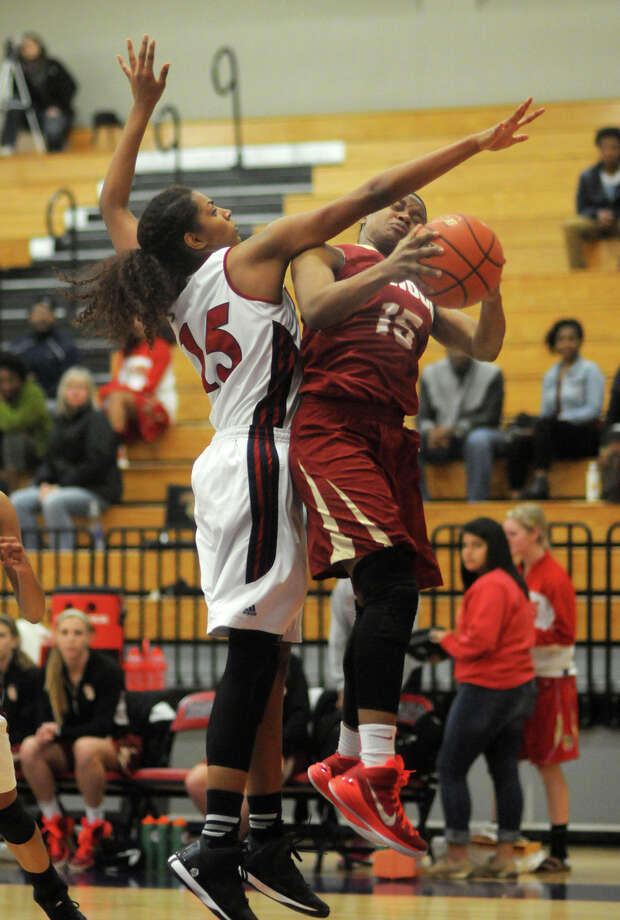 Atascocita junior Hannah Hopkins, left, blocks the path of Cy-Woods junior guard Jasmine Williams on a drive in the 4th quarter of their season-opener at Atascocita High School on Tuesday. Photo: Jerry Baker, For The Chronicle