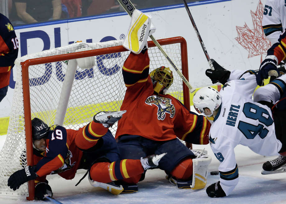 Tomas Hertl commits a roughing penalty that sends Scottie Upshall (19) sprawling beside Roberto Luongo. Photo: Lynne Sladky / Associated Press / AP